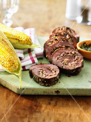 Steak roulade with chopped mushrooms, herb sauce and grilled corn cobs