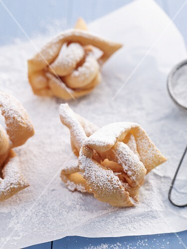 Crispy fried pasty with icing sugar on a piece of baking paper