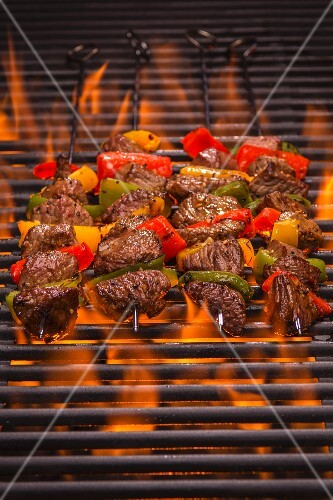 Beef skewers with peppers on a flaming grill