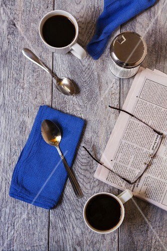 Breakfast for two with coffee cups, spoons, napkins, a sugar pot, a morning newspaper and a pair of glasses