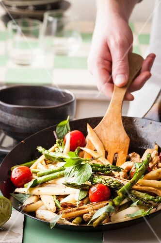 Fried asparagus with tomatoes and basil