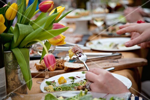 People eating outside at a table laid with large bunches of tulips