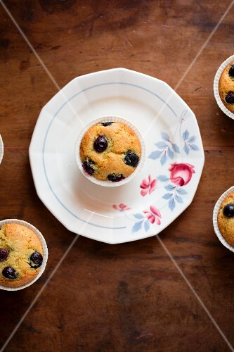 Blueberry muffins on a plate and on a wooden table