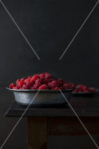 Fresh organic raspberries in a metal bowl on a wooden table