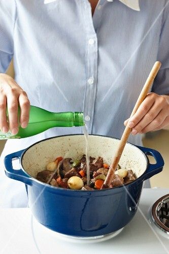Sake being poured over beef stew