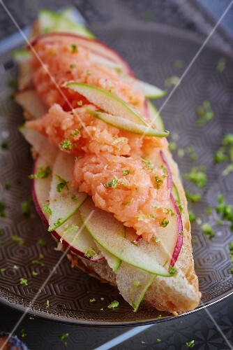 A slice of bread topped with apple and smoked salmon