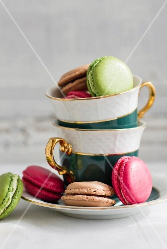 Various macaroons in a stack of porcelain cups