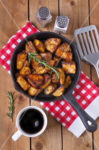 Spiced baked potatoes with rosemary in a cast iron pan