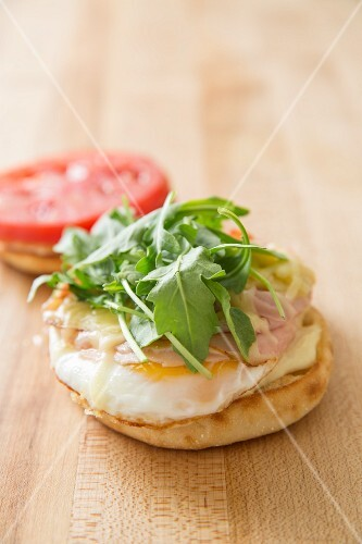 An English muffin with eggs, cheese, ham rocket and tomatoes for breakfast