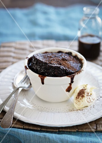 Chocolate soufflé with chocolate sauce and whipped cream
