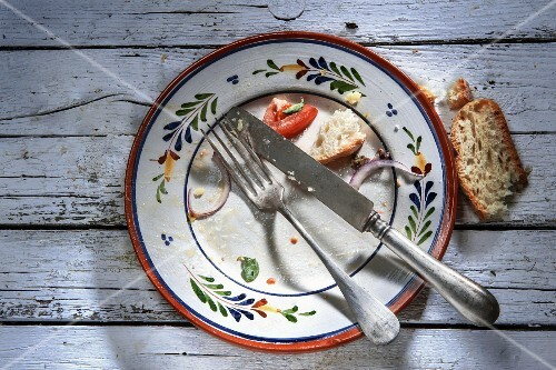 The remains of food and bread on an empty plate