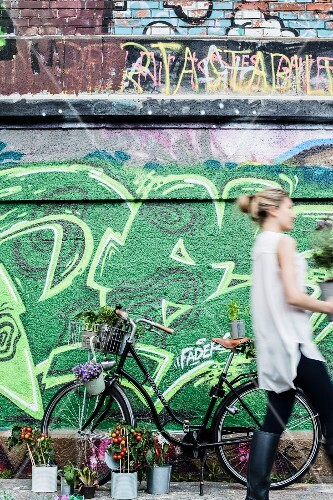 Bicycle decorated with plants in front of wall covered in graffiti
