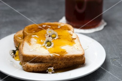 Slices of toast with honey and daises