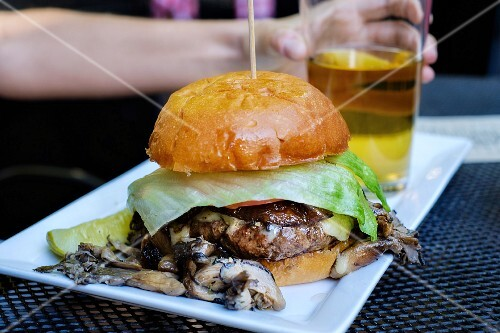 A burger with mushrooms with a glass of beer on a serving platter