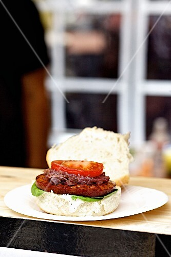 A sucuk burger on a wooden table