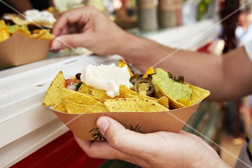 Tortilla chips with sour cream and guacamole at a market (Barcelona, Spain)