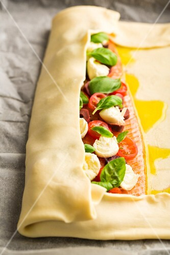 Alpine salmon with tomatoes, mozzarella and basil being wrapped in puff pastry