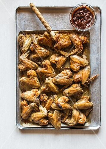 Chicken wings being brushed with marinade