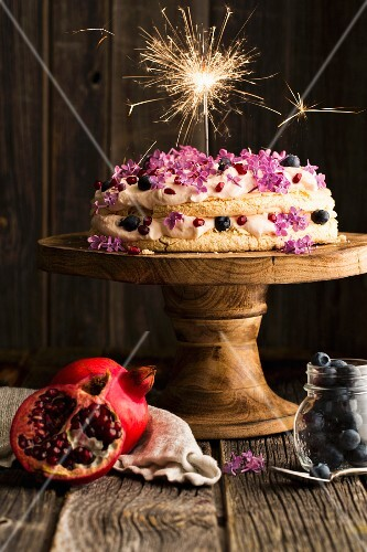 Pavlova with lilac flowers, blueberries and pomegranate seeds