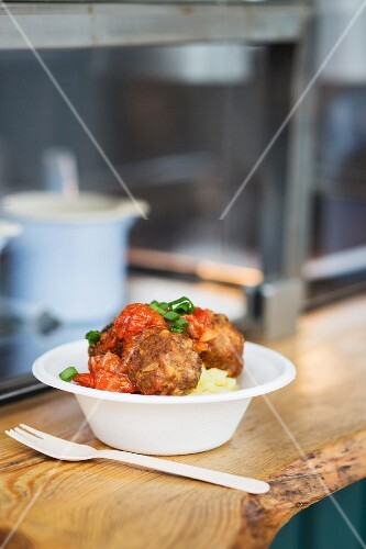 Mashed potato with meatballs on the counter of a fast food stand