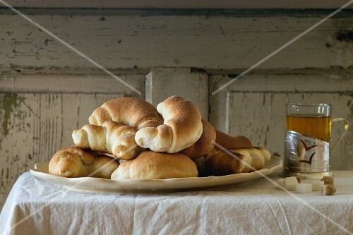 A plate of freshly baked homemade crescent rolls, served with a cup of tea on a white tablecloth