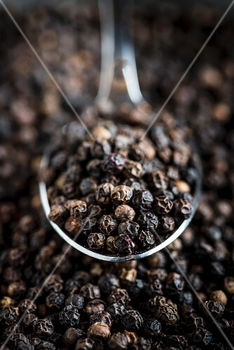 Black peppercorns on a spoon