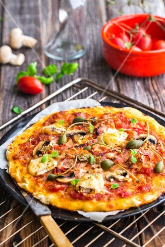 Gluten-free pizza with ham, Brie, mushrooms and capers