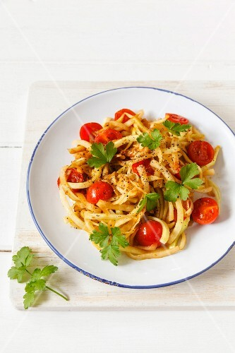Vegetable spaghetti made from kohlrabi with steamed cherry tomatoes and garlic