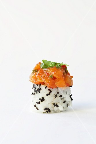 A rice canapé with black sesame seeds and salmon tatar
