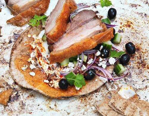 Pork belly on unleavened bread with cucumber and olives