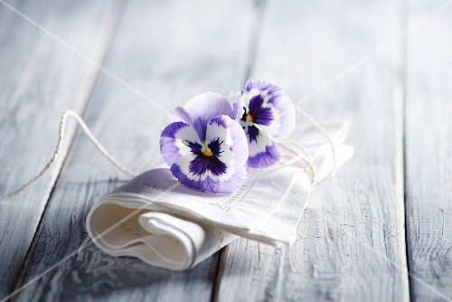 White linen napkin and violas on wooden surface