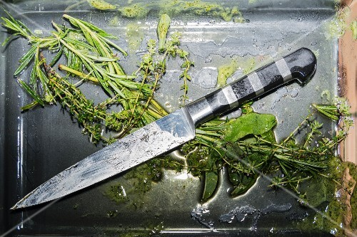 A herb marinade, herbs and a knife in a tub
