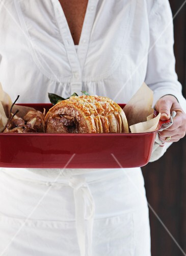 A woman holding a roast pork roulade in a roasting dish