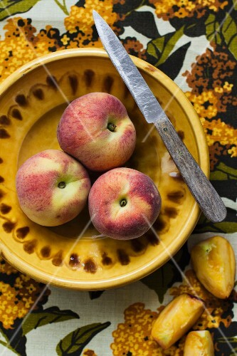 Fresh peaches with a knife on a yellow plate
