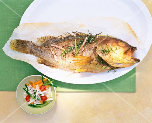 Grouper with rosemary on parchment paper