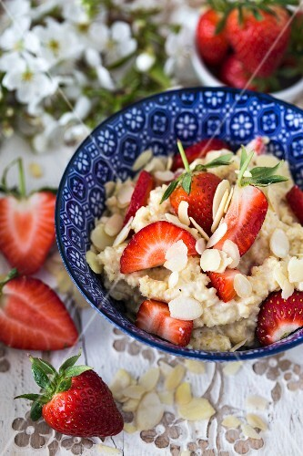 Millet porridge with fresh strawberries and flaked almonds