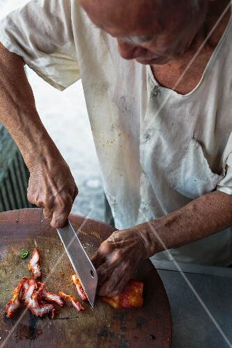 Pork being chopped at a market (Bangkok, Thailand)