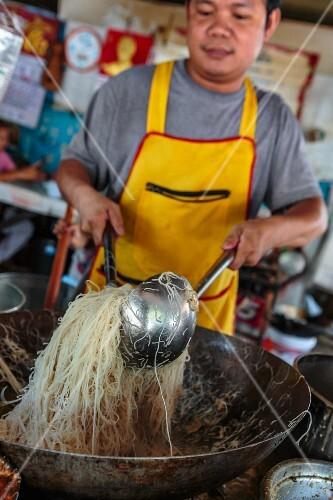 A man cooking rice noodles at a market (Bangkok, Thailand)