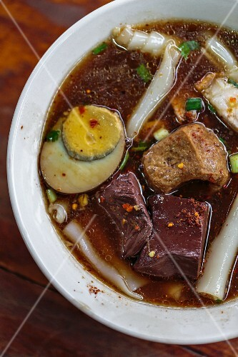 Rice noodle soup with boiled egg, black pudding and fried tofu (Bangkok, Thailand)