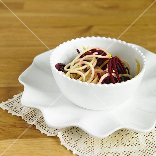 Vegetable spaghetti made from beetroot and yellow courgettes in a white bowl