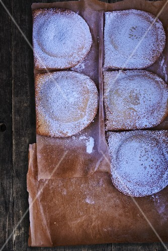 Chausson with icing sugar on a piece of baking paper