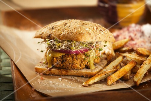 A vegan burger with bean sprouts and chips