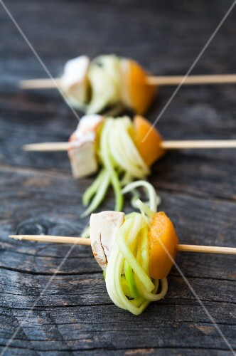 Skewers with rolled courgette noodles, peaches and cheese on a wooden surface