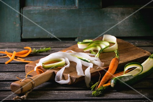 Grated vegetable noodles made from carrots, radishes and courgettes on a chopping board