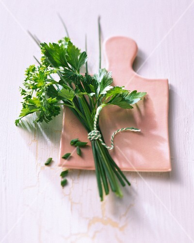 A bunch of fresh herbs on a chopping board
