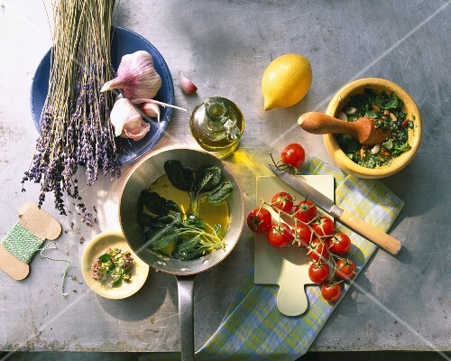 An arrangement of herbs, garlic, olive oil, lemon and cherry tomatoes