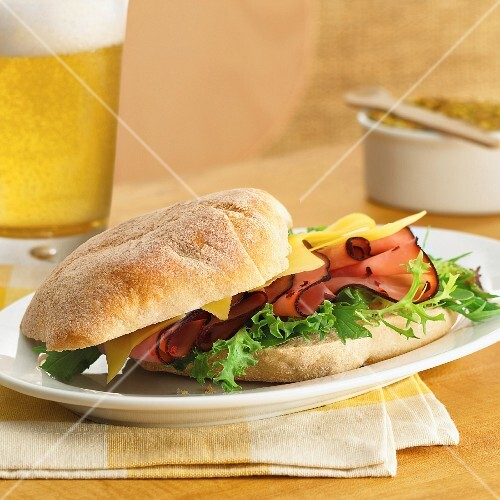 Ciabatta sandwich with roast beef and cheese served with a glass of beer