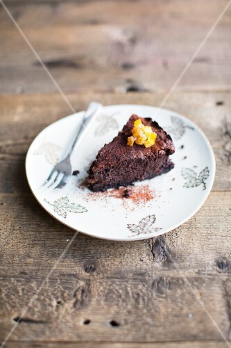 A slice of chocolate cake with candied orange peel