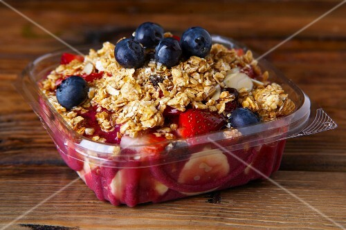 Muesli with strawberries and blueberries in a plastic container