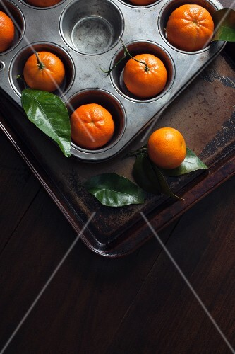 Clementines in a muffin tin and on a baking tray